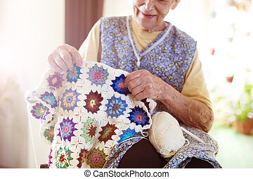 Old woman knitting - Old woman is knitting a blanket inside...