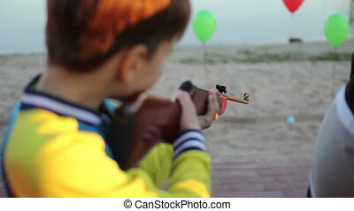 boy with rifle shooting at balloons