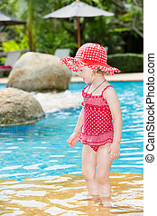Funny little child girl near swimming pool on tropical...