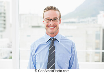 Smiling businessman with glasses standing in his office