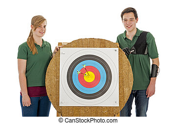 Boy and girl standing besides archery target - Young boy and...