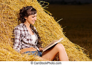 Girl reading book on haystack - Young girl reading book on...