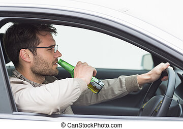 Man drinking beer while driving in his car