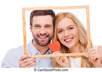 Celebrating their love. Beautiful young loving couple bonding to each other and holding heart shape paper while looking through a frame and standing isolated on white background