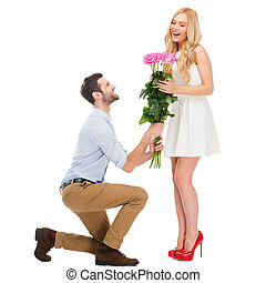 They are as beautiful as you! Full length of man standing at his knee and giving a bouquet of pink roses while both isolated on white background