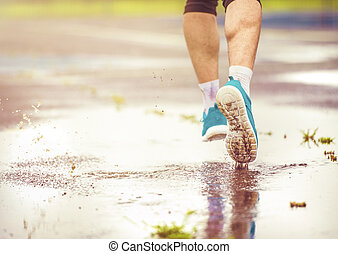 Young man running in rainy weather - Young man jogging on...