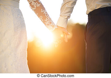 Young wedding couple holding hands as they enjoy romantic...