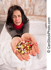 Frustrated woman lying in bed with pills - Sneezing woman...