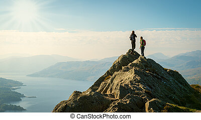 Two female hikers on top of the mountain enjoying valley...