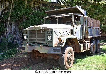 military truck parked in the grass in the sun