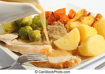 Pouring gravy on a roast turkey meal - Pouring gravy on a...