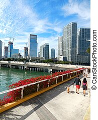 People walking on a sidewalk on along Biscayne Bay from...