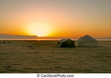 Yurts in Kyrgyzstan - Sun rising over traditional yurt of...