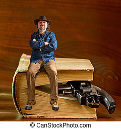 man sitting on the book and handgun