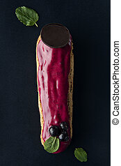 exquisite cream dessert eclair with blueberry and fresh mint...