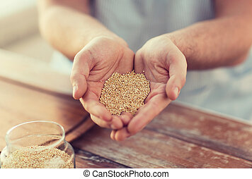 cloes up of male cupped hands with quinoa - cooking and home...