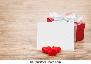 Blank valentines greeting card, gift box and red candy hearts