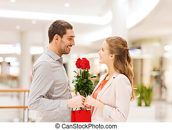 happy young couple with flowers in mall - relations, love,...