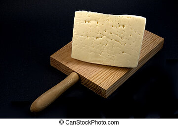 Table cheese. - Displays a cutting board with a piece of...