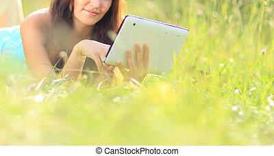 woman reading e-book - Happy woman reading e-book in the...