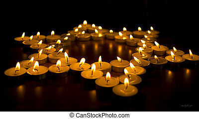 Burning Candles as a Star - Many burning candles arranged...