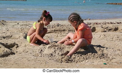 two little girls playing on beach near sea