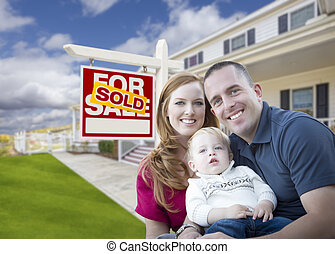 Young Military Family in Front of Sold Sign and House -...
