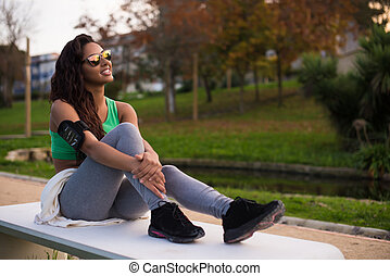 Fitness woman runner relaxing in the city park