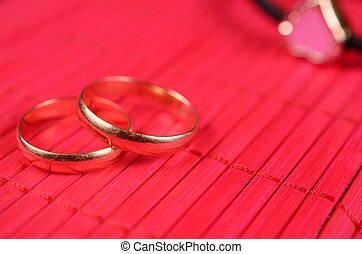 Orange gold-plated heart with two wedding rings on the red...