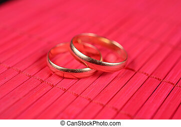 Two gold wedding rings on the red bamboo surface