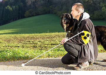 Attentive guide dog - A blind man kneels next to his...