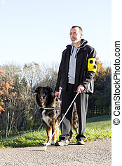 Man with his guide dog - A blind man goes for a walk with...