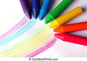 Oil pastel crayons lying on a paper with painted rainbow...