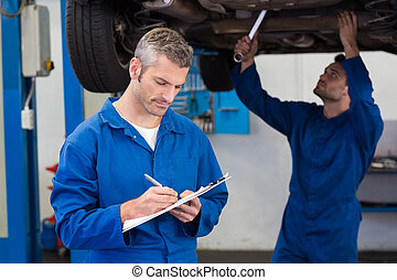 Team of mechanics working together at the repair garage