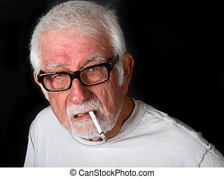 Elderly man smoking a cigarette with an angry look on his...