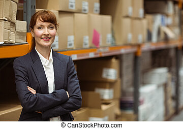 Pretty warehouse manager smiling at camera in a large...