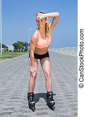 Fit blonde rollerblading on the promenade