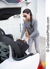 Woman pulling out a baggage of her car trunk in a car park