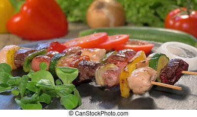 grilled meat skewers on stone plate - a table spread with...