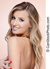 Jewelry - Young smiling blond lady on beige background