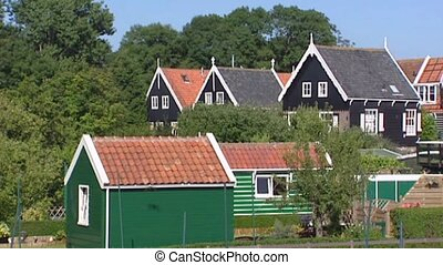 traditional green painted wooden houses at the Isle of...