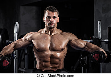 Fitness with dumbbells - Brutal athletic man pumping up...