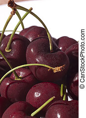 A clump of cherries. The cherries are wet with droplets, and...