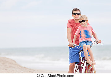 family biking at the beach - happy family of father and son...