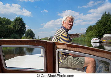 Man sitting on boat - Senior man making day trip on boat at...