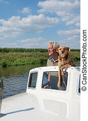 Man and dog in boat - Man and dog in motor boat on the river