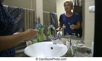 Woman Brushing Her Teeth - woman is standing in front of the...