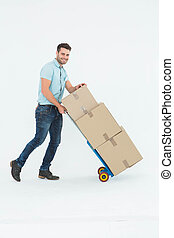 Happy delivery man pushing trolley of boxes - Full length...