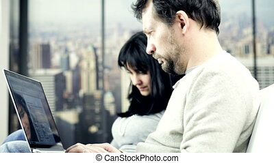 Couple at home working on sofa talking in New York