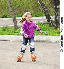 Little girl roller-skating in the park